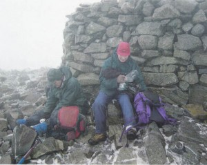 John and Allan take a lunch break in the snow (at what looks like the summit cairn on Scafell Pike)