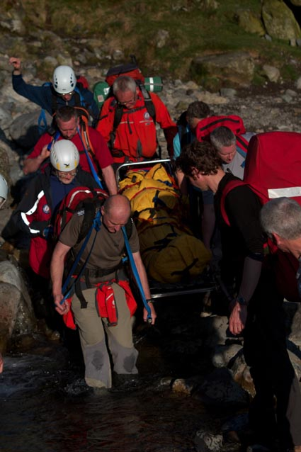 Team members carrying the stretcher through the beck