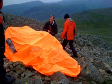 The casualty's leg is inspected by the team doctor under their very visible bivy tent