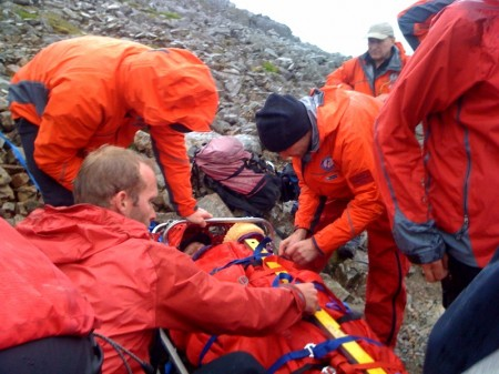 The casualty is strapped into the stretcher for the journey down