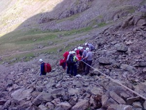The stretcher being carried down the scree with the safety of a backrope
