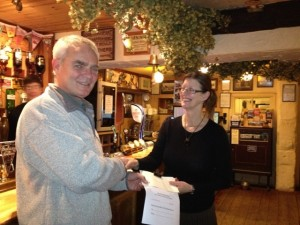 Team chairman Richard Warren accepting the cheque from Lesley at the  team dinner