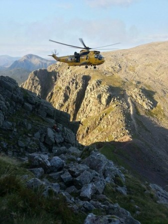 The Sea King lowering the winchman to the stuck climber.