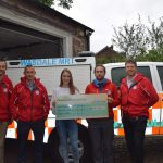Team members receive cheque from apprentice Abigail Elsworth